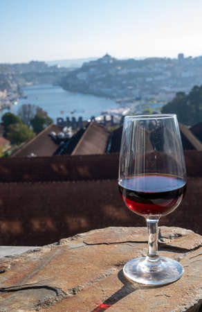 Tasting of different fortified dessert ruby, tawny port wines in glasses with view on Douro river, porto lodges of Vila Nova de Gaia and city of Porto, Portugal, close up