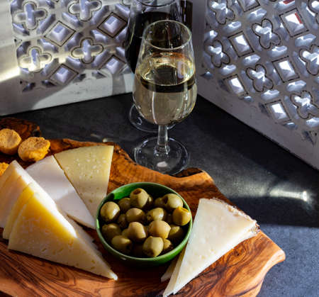 Tasting of fortified Andalusian dry fino and sweet sherry wine with traditional Spanisch tapas, green olives, goat and sheep manchego cheese Reklamní fotografie