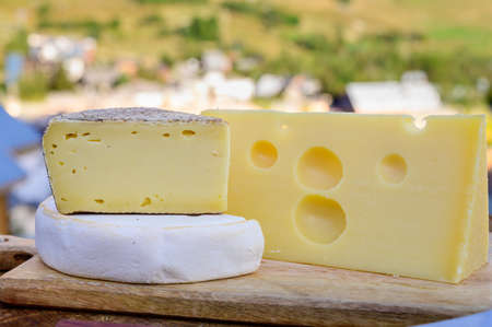 Cheese collection, French emmental, tomme and reblochon de savoie cheeses served outdoor in Savoy region, with Alpine mountains peaks in summer on background