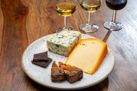 Tasting and pairing of different cheeses with strong alcoholic drinks, whiskey, cognac or calvados close up