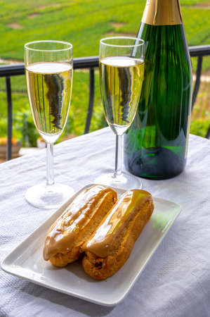 Taste of France, fresh baked eclair cakes with caramel cream with champagne traditional sparkling wine in glass and view on green vineyards of Champagne, France Imagens