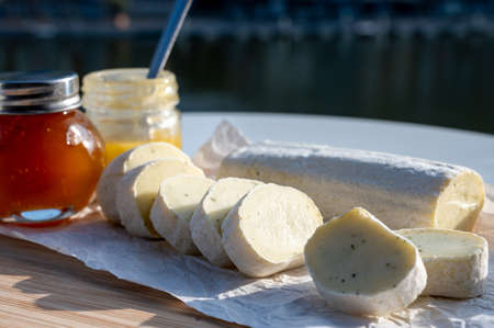 Belgian abbey cheese fagotin in pieces with jam served outdoor with nice view on Maas river and center of Dinant, Wallonia, Belgium