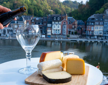 Pouring of strong Belgian abbey beer and tasting of cheeses made with beer and fine herbs with view on Maas river in Dinant, Wallonia, Belgium