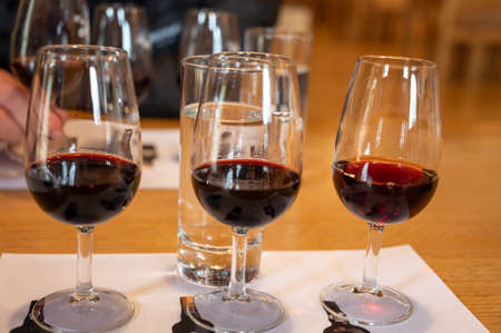 Professional tasting of different fortified dessert ruby, tawny port wines in glasses in wine cellars in Porto, Portugal, close up 版權商用圖片