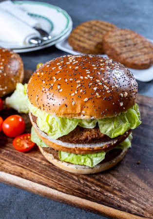 Lunch or dinner with tasty vegetarian burgers made from plant based grilled burgers, fresh bakes buns and organic vegetables close up
