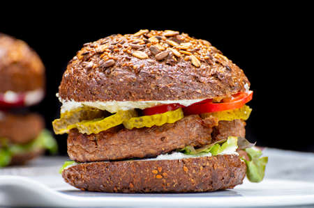 Vegan burgers with grilled healthy plant based, meat free burgers and fresh vegetables