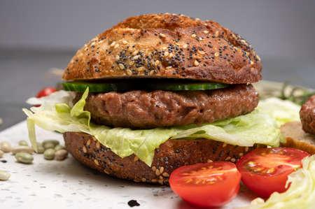 Making tasty vegetarian vegan hamburger from plant based soya beans burger, organic bun with seeds and fresh garden vegetables