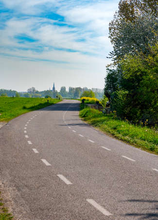 Spring nature landscape with dam road along Waal river in sunny day in Betuwe, Gelderland, Netherlands