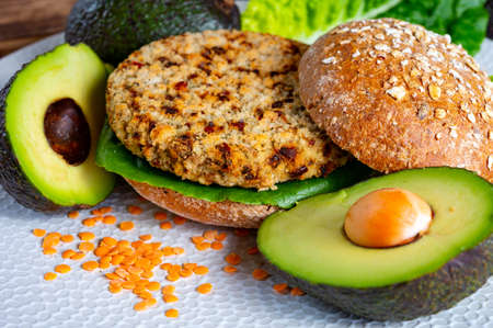 Tasty vegetarian healthy green food, homemade burgers made from orange lentils legumes with green lettuce and fresh ripe avocado Reklamní fotografie