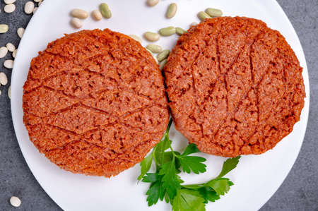 Tasty uncooked burger made with vegetarian plant based imitation minced soya beans meat ready for grill