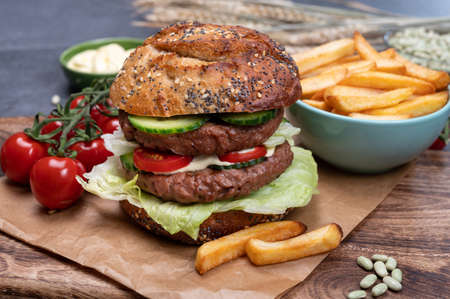 Making tasty vegetarian vegan lunch with double decker hamburger made from plant based soya beans burger, organic bun with seeds and fresh garden vegetables and french fried potatoes