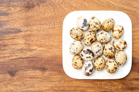 Fresh small spotted partridge eggs on white board close up Фото со стока