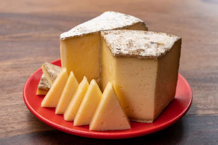 Cheese collection, Tomme de Savoie cheese from Savoy region in French Alps, mild cow's milk cheese with beige interior and thick brownish-gray rind close up