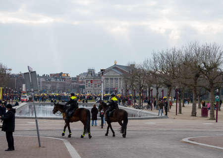 March 7, 2021, Amsterdam, Netherlands, Yellow umbrella's protest against covid-19 measures of Dutch government and vaccination