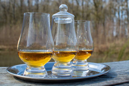 Tasting glasses of finest scotch whiskey strong drink on old outdoor wooden table Stock Photo