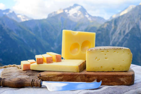 Cheese collection, French beaufort, abondance, emmental, tomme de savoie cheeses served outdoor in Savoy region, with Alpine mountains peaks in summer on background