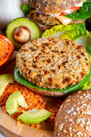 Tasty vegetarian healthy green food, homemade burgers made from orange lentils legumes with green lettuce and fresh ripe avocado