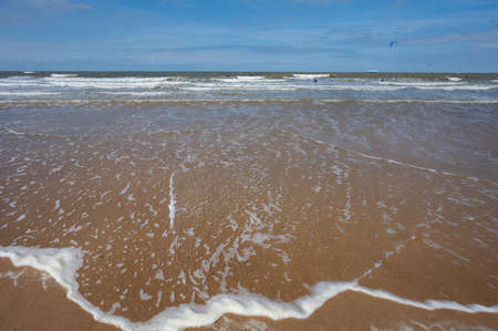 North sea waves and sandy beach in sunny day and blue sky