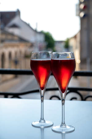 Drinking of Kir Royal, French aperitif cocktail made from creme de cassis topped with champagne, typically served in flute glasses, with view on old French village Stock fotó