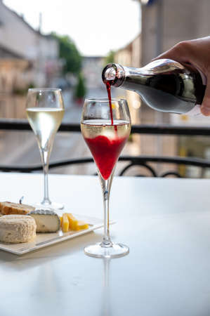 Drinking of Kir Royal, French aperitif cocktail made from creme de cassis topped with champagne, typically served in flute glasses, with view on old French village