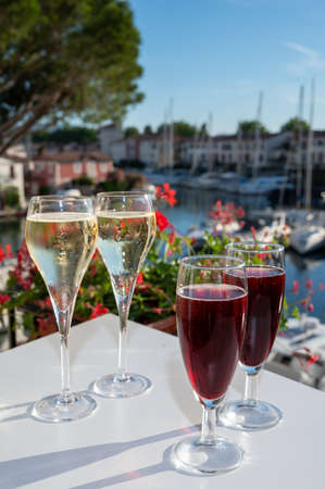 Summer party with kir royal cocktail, tasting of French brut champagne sparkling wine and cold creme cassis in glasses in yacht harbor of Port Grimaud near Saint-Tropez, French Riviera vacation, France Stock fotó