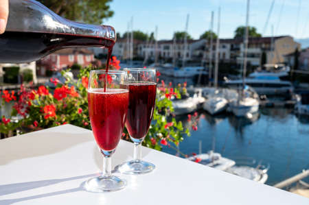 Summer party with kir royal cocktail, pouring of French brut champagne sparkling wine and creme cassis in glasses in yacht harbor of Port Grimaud near Saint-Tropez, French Riviera vacation, France Stock fotó