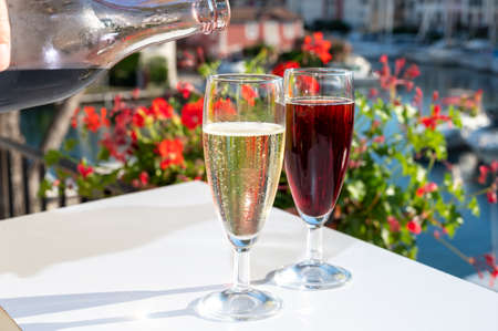Summer party with kir royal cocktail, pouring of French brut champagne sparkling wine and creme cassis in glasses in yacht harbor of Port Grimaud near Saint-Tropez, French Riviera vacation, France