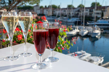 Summer party with kir royal cocktail, tasting of French brut champagne sparkling wine and cold creme cassis in glasses in yacht harbor of Port Grimaud near Saint-Tropez, French Riviera vacation, France
