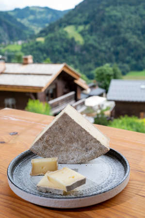 Cheese collection, French cheese tomme de savoie and french mountains village in Haute-Savoie in summer on background Stock fotó