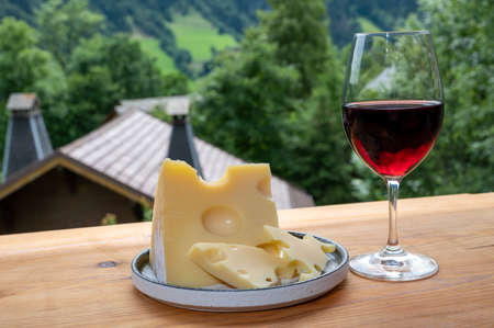 Cheese collection, French cow cheese emmental, glass of red wine from Savoie and french mountains village in Haute-Savoie in summer on background