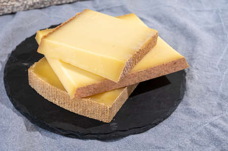 Cheese collection, hard French cheese comte made from cow milk with rind in Franche-Comte region, France close up