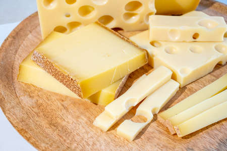Cheese collection, hard French cheeses comte and emmentaler with round holes made from cow milk close up Banque d'images