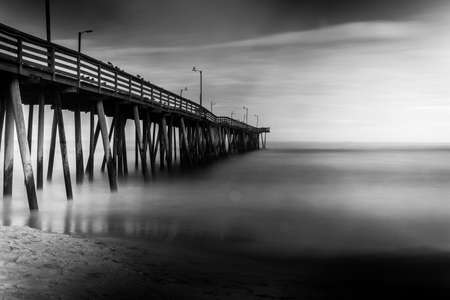 oceanfront: Long exposure of water hitting the oceanfront pier. Stock Photo