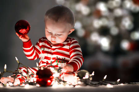 Cute infant playing with Christmas lights and decorations.