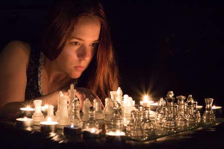 luz de velas: Mujer jugando al ajedrez luz de las velas.