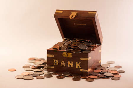 Overflowing wooden bank of change against a white background.