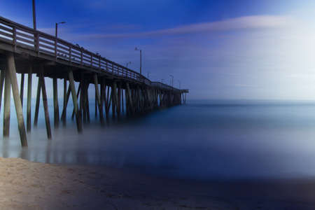 Long exposure of water hitting the oceanfront pier. Stock Photo