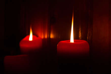 candlelit: 3 red burning candles lighting the darkness.