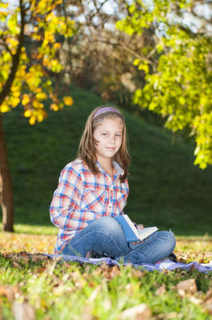 Girl with a book in the park photo