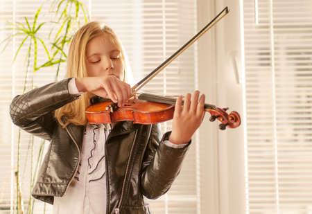 violin making: Girl playing the violin at the window