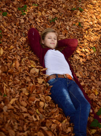어린 소녀: Little girl in autumn orange leaves. Outdoor.