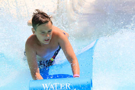pool water: Faliraki,Rhodes,Greece-Julyt,25,2015:Young boy on the mat racer slide in Water park,Mat racer slide is very popular for young people in the Water Park.Water Water Park is located in Faliraki on the island of Rhodes in Greece and one of the most largest in