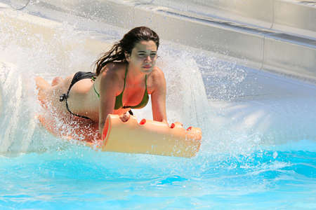 brethren: Faliraki,Rhodes,Greece-August,25,2015:Young happy girl gets into pool after landing on the mat racer slide.Mat racer slide is very popular for young people in the Water Park.Water Water Park is located in Faliraki on the island of Rhodes in Greece and one Editorial