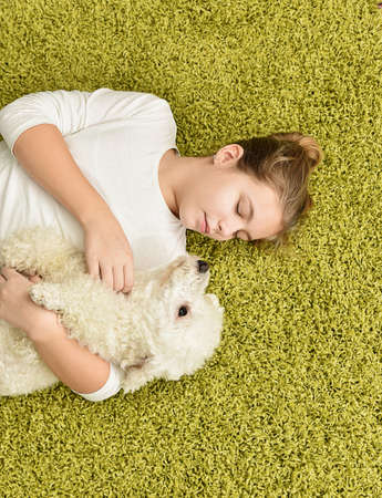 white poodle: Girl with white poodle playing on the green carpet
