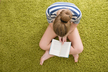 green carpet: Girl with the book oh the green carpet Stock Photo