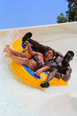 Faliraki,Rhodes, Greece-July 2,2016:Boyfriend and a Girlfriend in a very interesting way drive with tube on the rafting slide in the  Water park.Rafting slide is one of many popular game for adults and children in park.Water Water Park is located in Falir