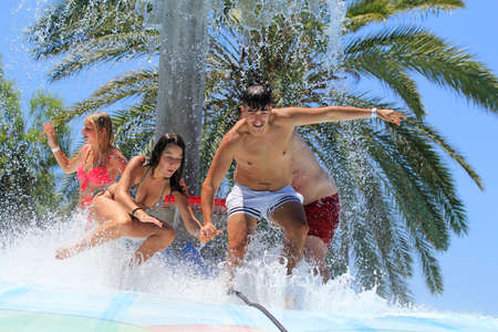 Faliraki,Rhodes, Greece-Jun 5,2016:Cheerful group of young people jumping on the wet bubble in the  water park  .Wet bubble is one of many popular game for adults and children in Water park..Water Park is located in Faliraki on the island of Rhodes in Gre Editorial