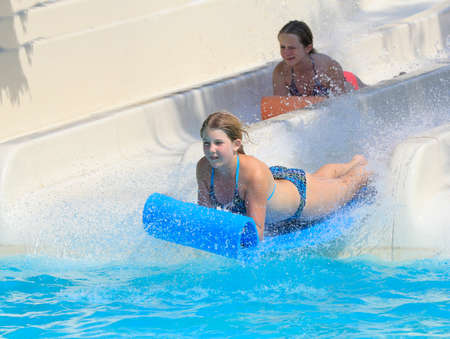 Rhodes,Greece-August 1,2016: Two girl on the mat racer slide.Mat racer slide is very popular for young people in the Water Park. Water Park is located on the island of Rhodes in Greece and one of the most largest in Europe and is a very popular place for