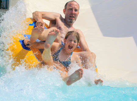 douther: Rhodes, Greece-August 1,2016:Father and douther on the rafting slide in the  Water park.Rafting slide is one of many popular game for adults and children in park. Water Park is located on the island of Rhodes in Greece and one of the most largest in Europ Editorial