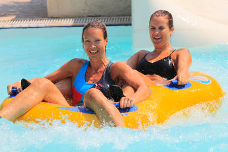 douther: Rhodes, Greece-August 1,2016:Mather and douther after rafting slide in the  Water park.Rafting slide is one of many popular game for adults and children in park. Water Park is located on the island of Rhodes in Greece and one of the most largest in Europe